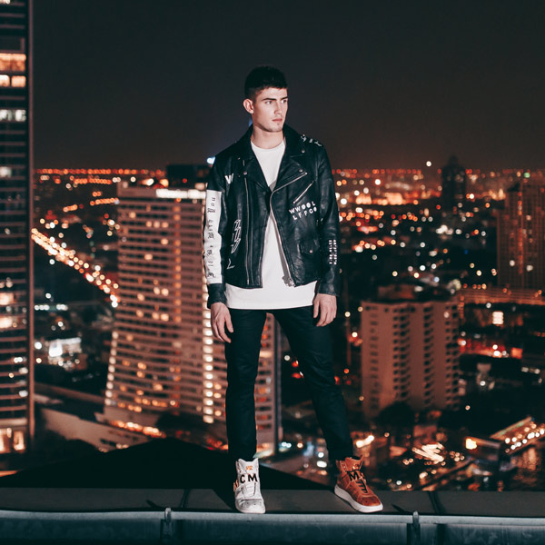 Robin Packalen standing on a roof with Bangkok skyline during the night